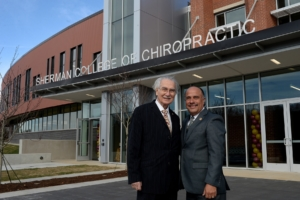 Dr. Thom Gelardi, Sherman College founder, and Dr. Edwin Cordero, Sherman College president stand in front of the newly completed Gelardi Student Center at Sherman College of Chiropractic.